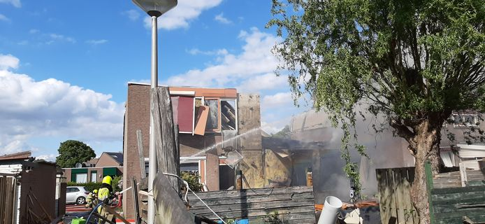 De brandweer blust de woning die na de explosie in brand vloog in Hillekensacker.