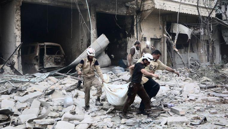 Leden van de Syrian Civil Defense, beter bekend als de White Helmets, halen een lijk van onder het puin in Aleppo. Beeld Belgaimage