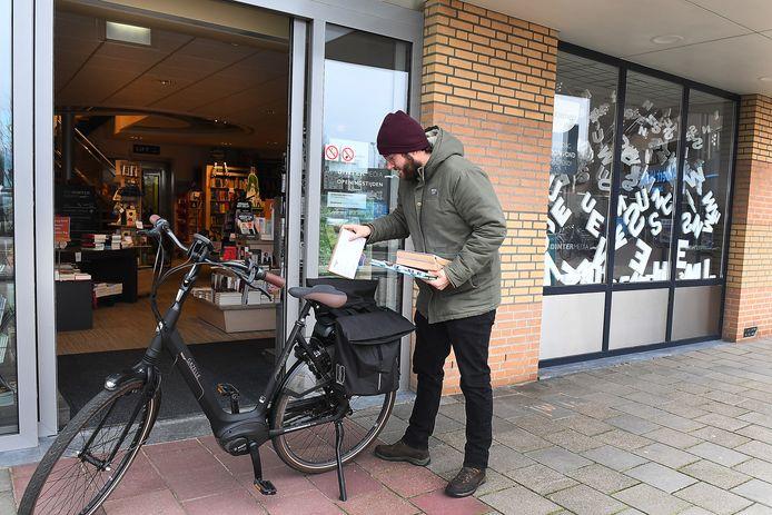 Joris van den Berg gaat op de fiets boeken bezorgen die bij van Dinter zijn besteld.