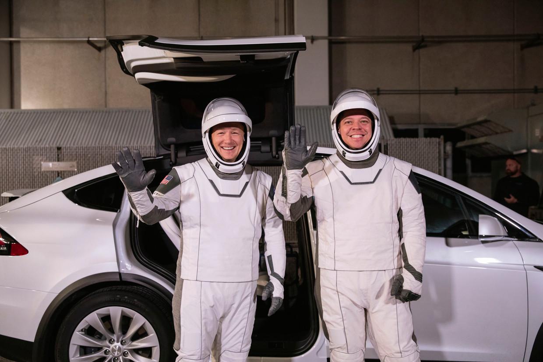 Astronauten Doug Hurley (links) and Robert Behnken poseren voor een Tesla Model X. Beeld AP