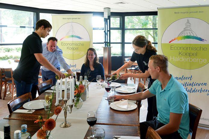 Kay-Dee (l) en Ivy schenken de wijn in. Tim Berendsen geeft instructies.