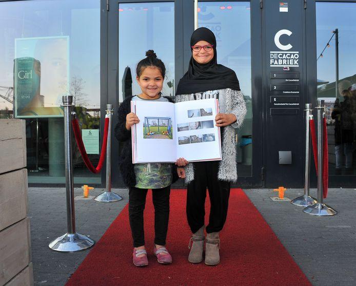 De 9-jarige Yessira Feghouli en haar 6-jarige zusje Noorsien tonen trots het fotoboek met daarin de foto's van Yessira.