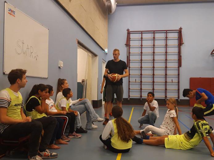Bart van der Horst geeft uitleg aan het basketbalklasje.