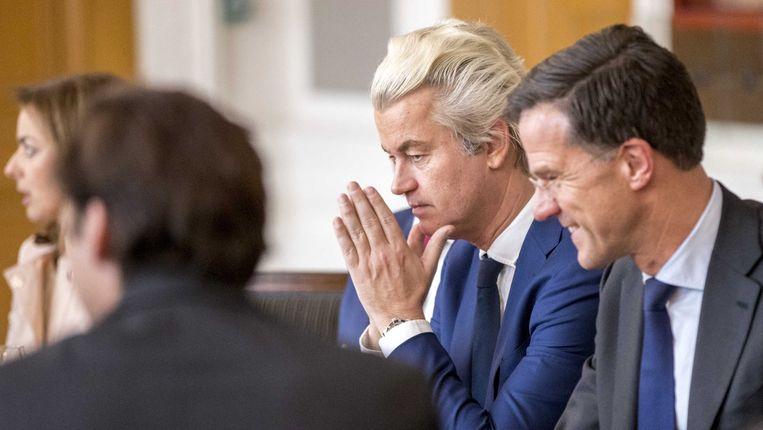 Geert Wilders (PVV), geflankeerd door Mark Rutte (VVD), wrijft zich in de handen tijdens een meeting in Den Haag. Beeld ANP