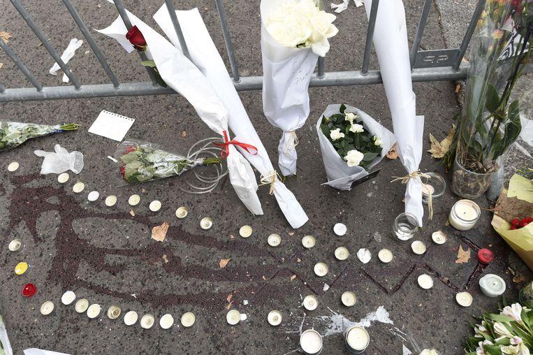 Kaarsen en bloemen aan bloedsporen aan concertzaal Bataclan.