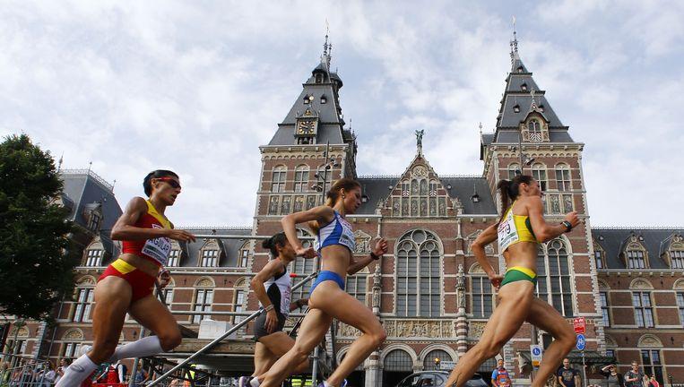 Atletes passeeren het Rijksmuseum. Beeld ap