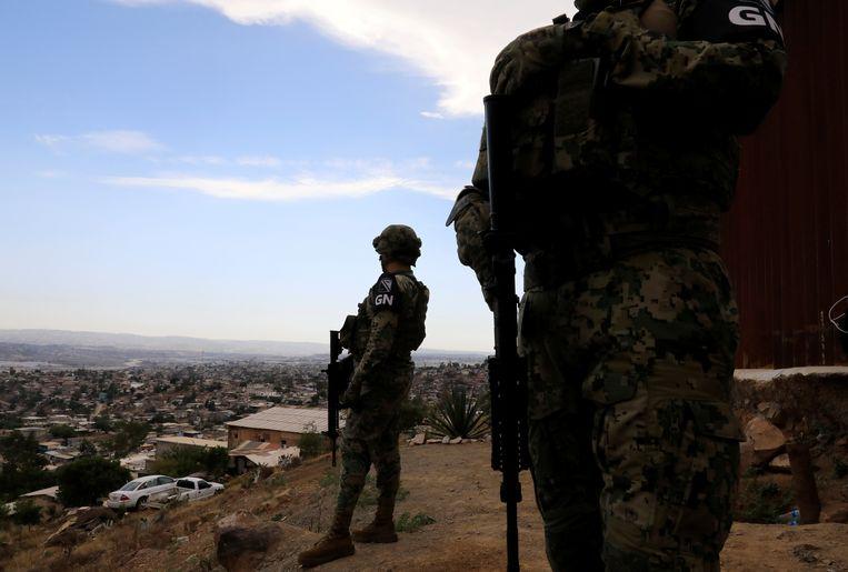 Leden van de nationale garde bij een grenshek tussen Mexico en de VS in Tijuana.