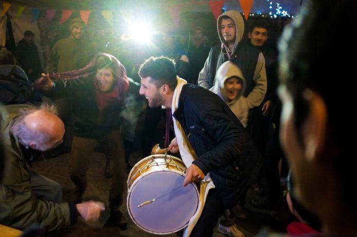 Ambiance in één van de geïmproviseerde feesttenten. Een bejaarde Franse bezoeker (links) laat zich meeslepen op het Arabische ritme.