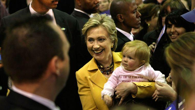 Hillary Clinton met een kind op de arm tijdens haar campagne Beeld ANP