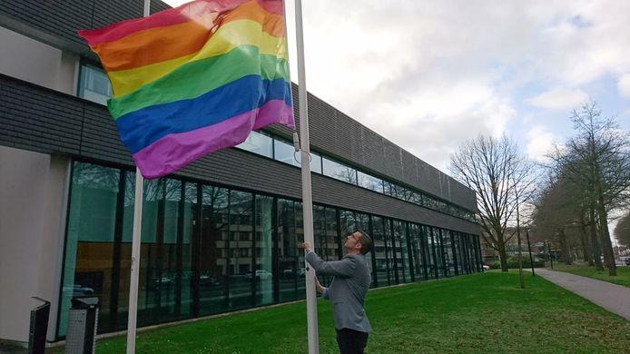 Wethouder Thijs van Kessel - een van de gasten van de talkshow - hijst in 2019 de regenboogvlag voor de ingang van het Osse gemeentehuis