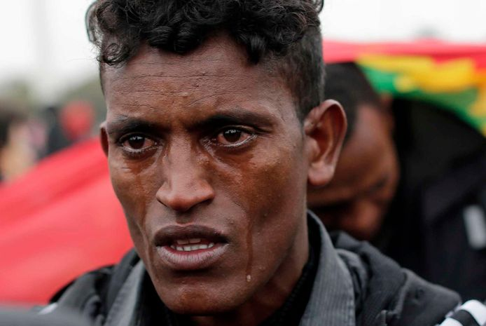 Een migrant uit Ethiopië huilt terwijl hij het kamp verlaat.