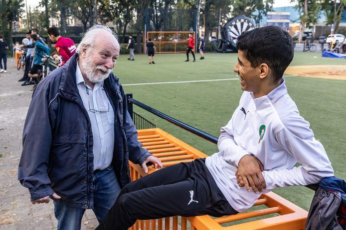 Buurtbewoner Wim Veen vond de door jongeren zelf  georganiseerde buurtbarbecue in de omgeving van het Cruyff Court aan de Hobodreef een fantastisch initiatief en hij ging graag in gesprek met de jeugd. Hier met Naoufal Chouiter.