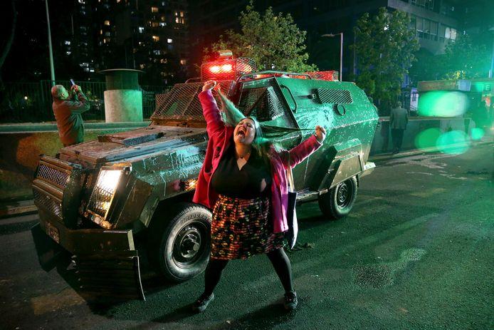 En boze betoger trekt aan haar haren en schreeuwt het uit bij een gepantserde politiewagen.