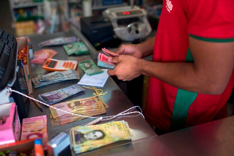 Een Braziliaanse winkelier telt Venezolaans geld aan de grens.