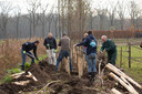 Vrijwilligers van Intents en Duurzaamheidsvallei aan het werk om het retentiebekken achter Sportpark Den Donk in het groen te zetten