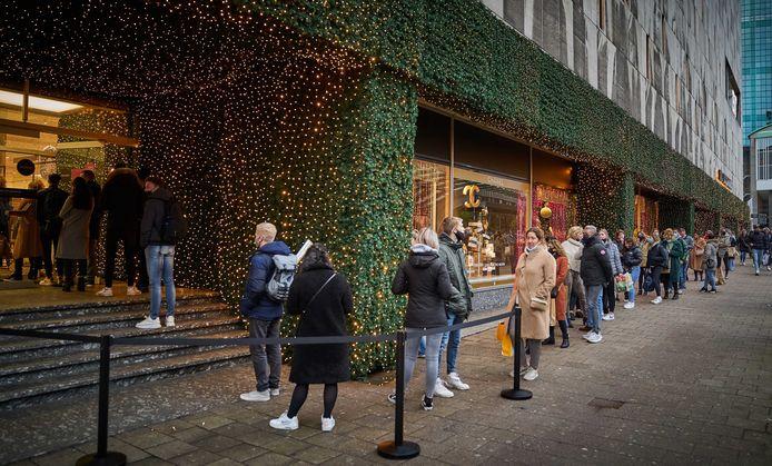 Lange rijen winkelend publiek bij de Bijenkorf.