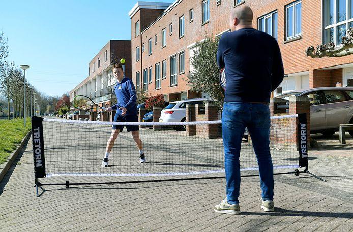 Tennisser Colin Standaart slaat een balletje met zijn vader op straat.