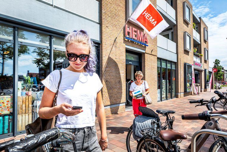 Bij de Hema in Vlijmen bekijkt Lotte Vrij (21) de sleutelhanger die ze voor haar vaders verjaardag heeft gekocht. Op de achtergrond mevrouw Van den Ende die zojuist een opblaasbaar zwembadje heeft gekocht. Beeld Raymond Rutting / de Volkskrant