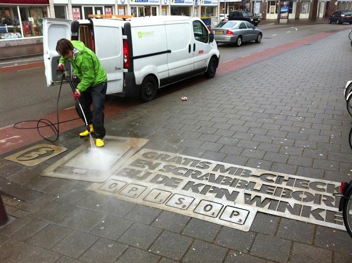 De reclame van KPN wordt in het wegdek gespoten in de binnenstad van Arnhem. foto Marco Bouman/DG