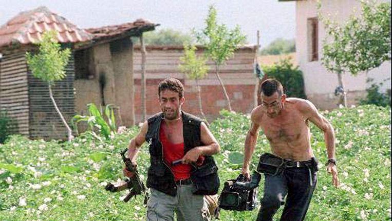 Een cameraman zoekt samen met een strijder van het Bevrijdingsleger van Kosovo dekking tijdens de oorlog in de regio Kosovo in 1998. Beeld epa