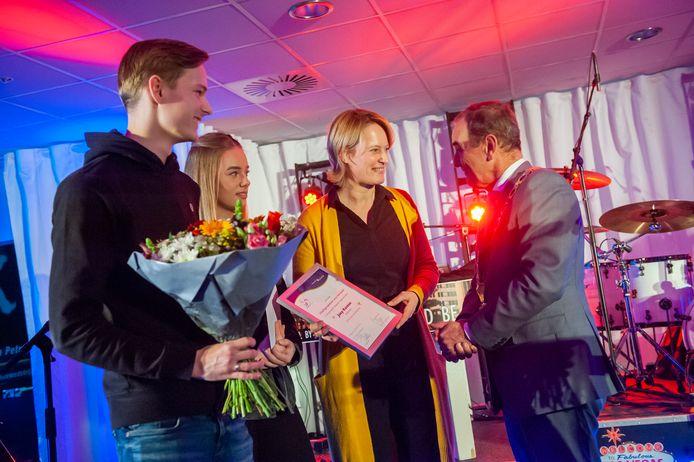 Nicole Koenen en kinderen Christie en Jesper ontvangen de prijs voor hun man en vader Joop Koenen uit handen van burgemeester Nol Kleijngeld.