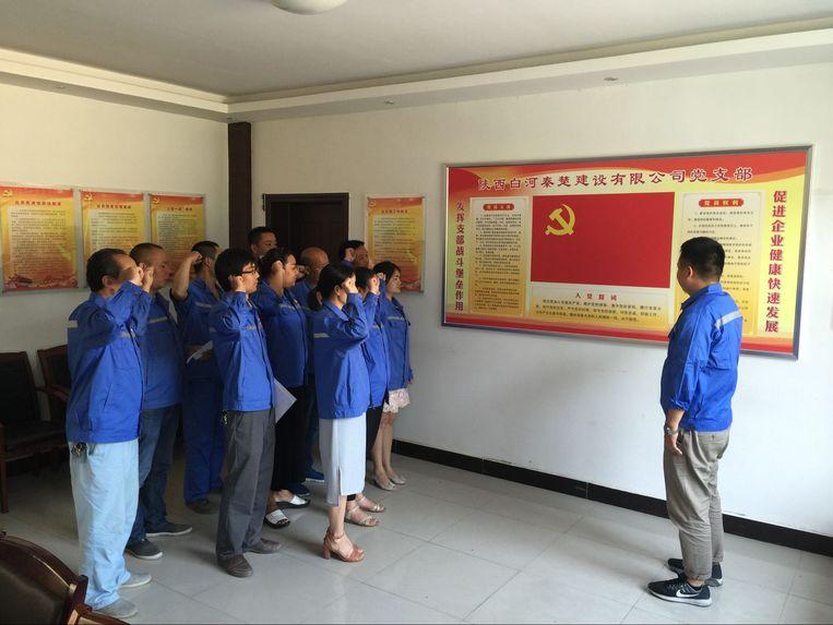 Werknemers van Qinchu leggen de partijeed af.  Beeld Leen Vervaeke