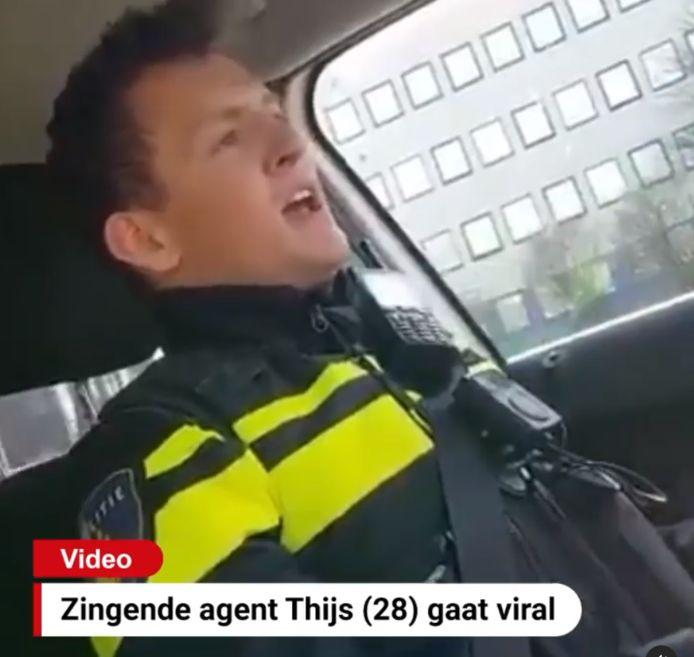 De jonge agent zingt vrolijk mee met de hit van Queen in de auto
