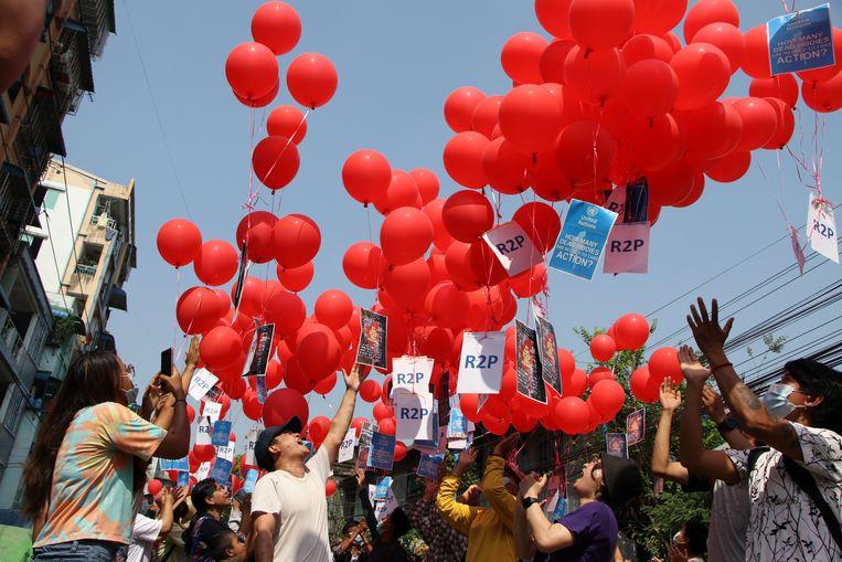 Met rode ballonnen uiten de inwoners van Yangon hun ongenoegen. Beeld AP