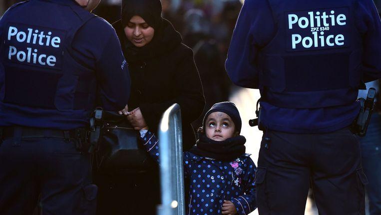 Beeld van de politie en een gezin uit Molenbeek op de solidariteitswake in de Brusselse gemeente gisteren. Beeld AFP
