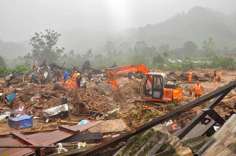 Reddingswerkers zoeken naar overlevenden tussen het puin na een aardverschuiving veroorzaakt door hevige regenval in Zuid-India.  Beeld REUTERS