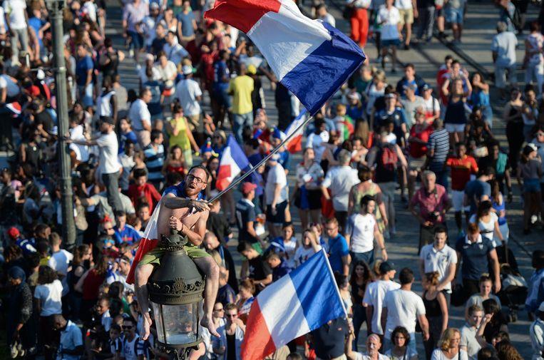 Een Franse fan klimt met de nationale driekleur in een lantaarnpaal.