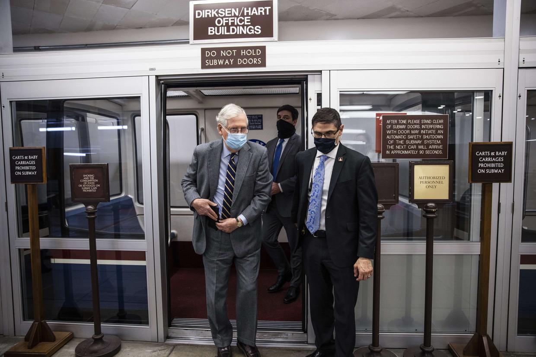 De Republikeinse leider in de Senaat, Mitch McConnell (links op de foto) dinsdag onderweg naar het Capitool in Washington, waar hij ondanks zijn aanvankelijke veroordeling van Trumps 'leugens', toch tegen diens impeachment zal stemmen. Beeld AFP