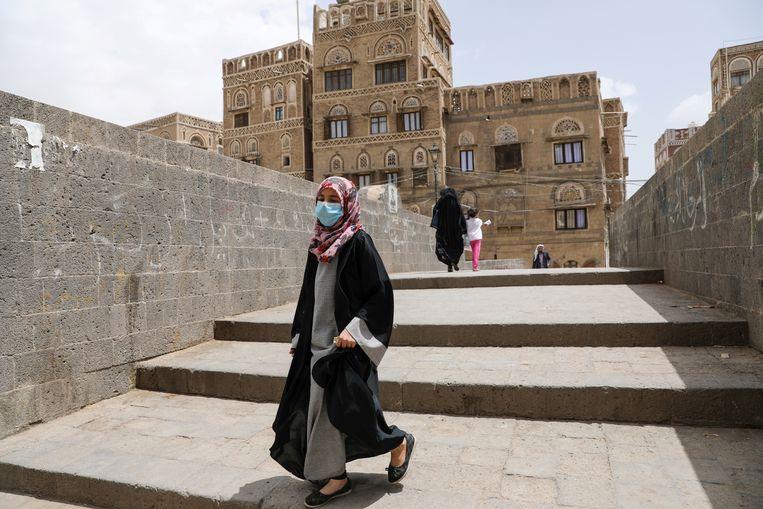 Een vrouw draagt een mondmasker in de Jemenitische hoofdstad Sanaa. Beeld REUTERS