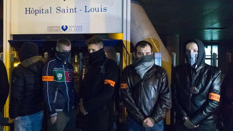 Een zestigtal andere agenten troepte gisteravond samen aan het ziekenhuis in Parijs, waar hun 28-jarige collega nog altijd in een kunstmatige coma wordt gehouden na de aanval van 8 oktober. Beeld AFP