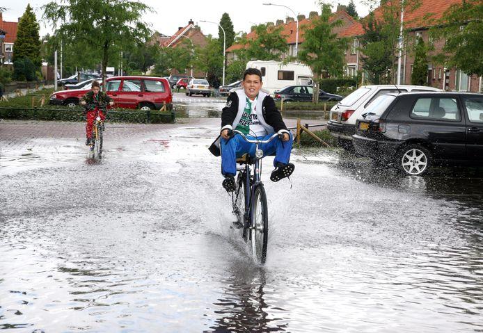 Twee jongens laten zich niet afschrikken door de 'binnenzee' in de Bosbesstraat in Nijmegen na een hoosbui.