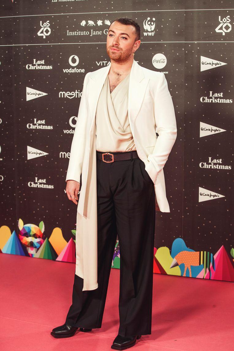 Sam Smith met gedrapeerde top en wijde broek.  Beeld Getty Images