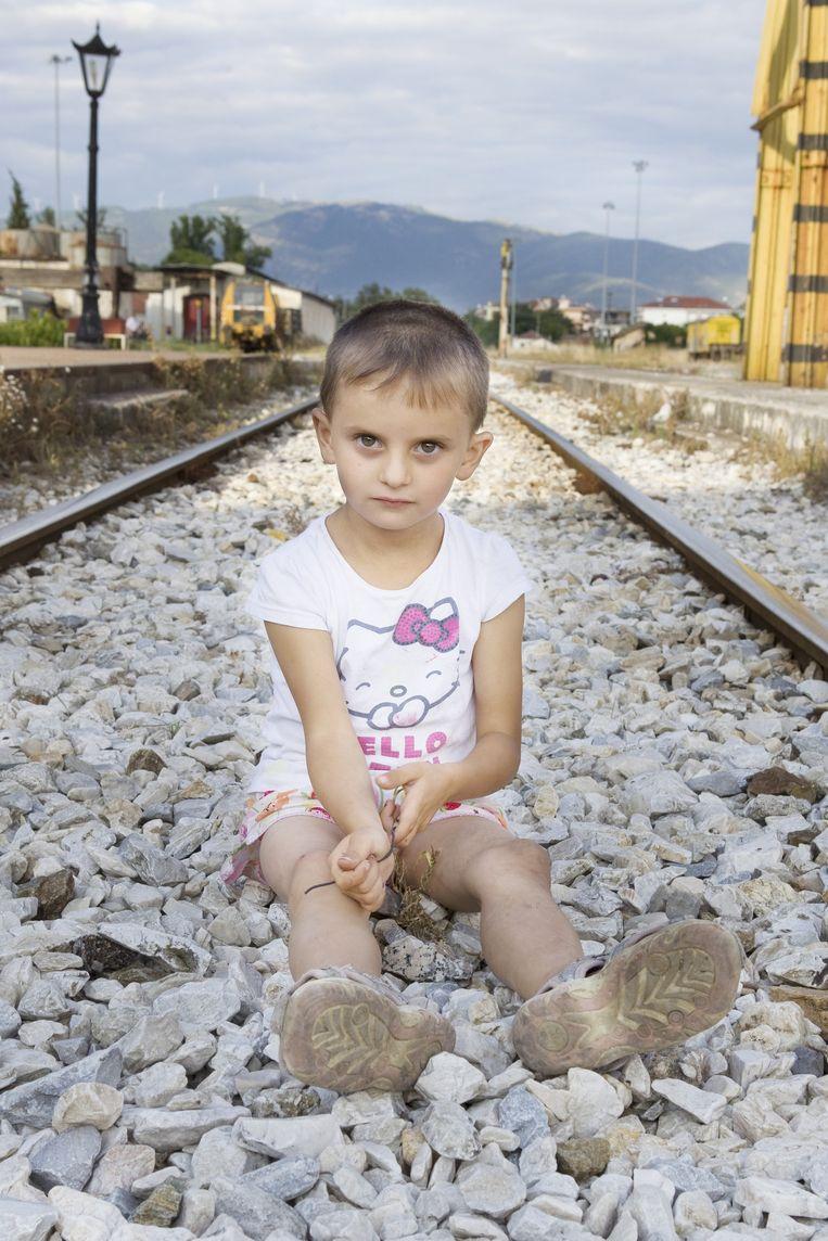 Bulgaars meisje speelt met de stenen op de treinsporen in afwachting van de trein. Beeld Io Cooman.