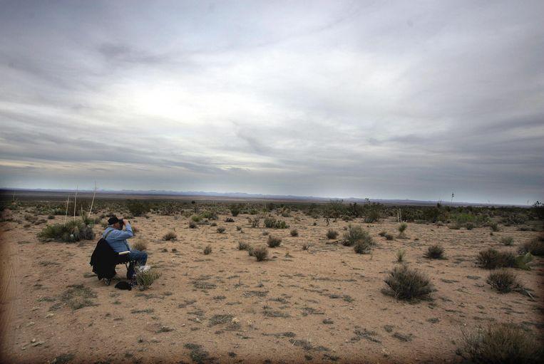 Een medewerker van het Minuteman-project speurt vanuit een observatiepost in de woestijn van New Mexico de horizon af op zoek naar immigranten die illegaal de grens proberen over te steken. Beeld AFP