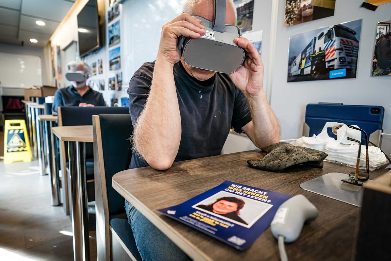 In een mobiel medialab van de politie kunnen bezoekers van de kermis in het Nederlandse Budel met een VR-bril 32 jaar terug in de tijd, naar de ochtend dat de vermoorde Wies Hensen werd gevonden. Beeld ANP