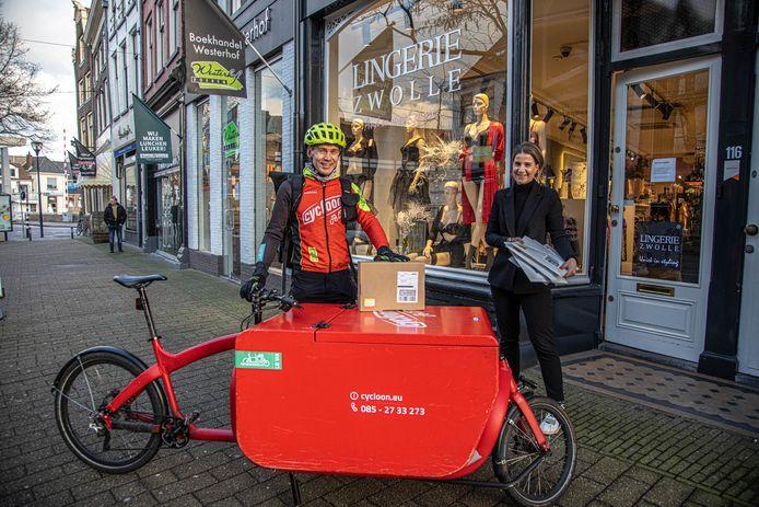 Lingerieverkoopster Van der Veen geeft pakketjes af aan een fietskoerier.