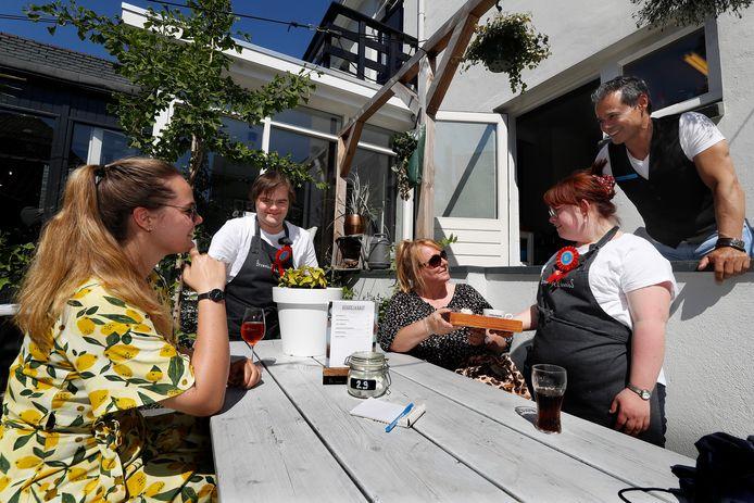 Medewerkers Daniël en Daisy (rechts) bedienen gasten bij Brownies&downieS in Zevenaar tijdens het eerste lustrum. Eigenaar Ralph de Nijs kijkt tevreden toe.