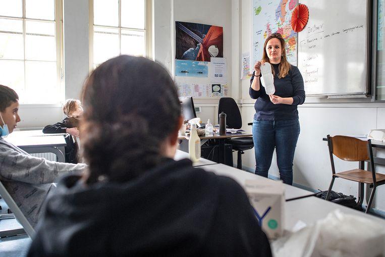 Docent Daantje Versteeg demonstreert tijdens de les over Dolle Mina hoe maandverband werkt. 'Menstruatie is misschien wel het grootste taboe.'  Beeld Guus Dubbelman / de Volkskrant