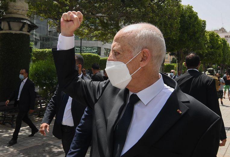 De Tunesische president Kais Saied heft een gebalde vuist naar omstanders tijdens een recente wandeling in de hoofdstad Tunis. Deze foto is verspreid door zijn kantoor. Beeld AP