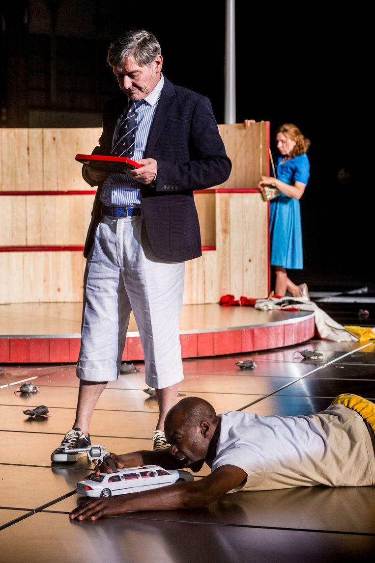 Pierre Bokma als miljardair in 'Kosmopolis', met Mandela Wee Wee aan zijn voeten en Elsie De Brauw op de achtergrond. Het stuk is een bewerking van het boek 'Cosmopolis' van 2003. Het gaat over een man in een (financiële) crisis. Beeld Ben van Duin