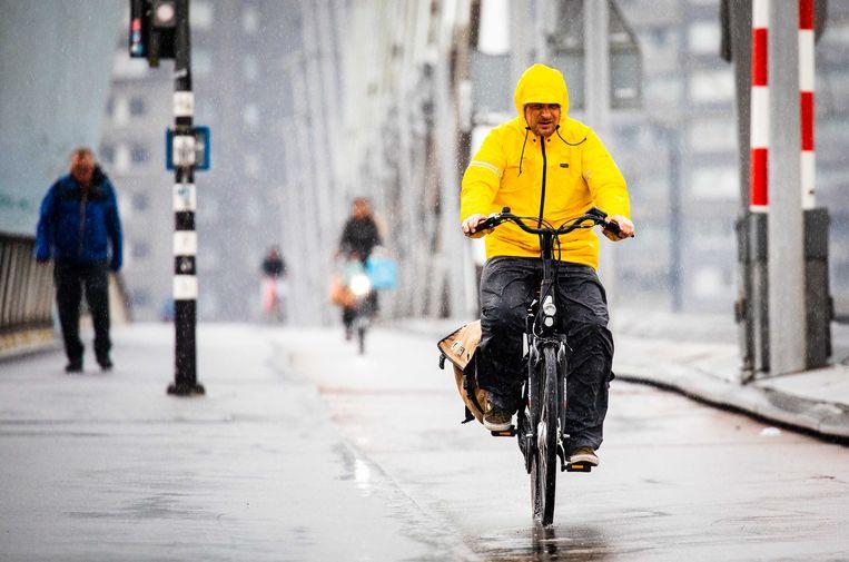 Een fietser op de Erasmusbrug tijdens een regenbui.  Beeld ANP
