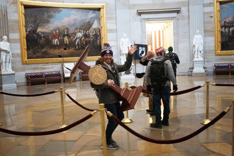 Een binnengedrongen Trumpaanhanger poseert met de katheder van Nancy Pelosi, de voorzitter van het Huis van Afgevaardigden. Beeld Getty Images