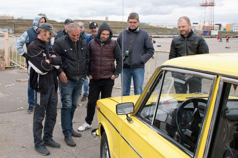 In Togliatti op de racebaan/circuit direct achter de Lada-fabriek. De voorzitter van de Russische Lada fanclub (geheel rechts) showt zijn oude, opgeknapte Lada aan een aantal geïnteresseerden. Beeld Sandra Hazenberg