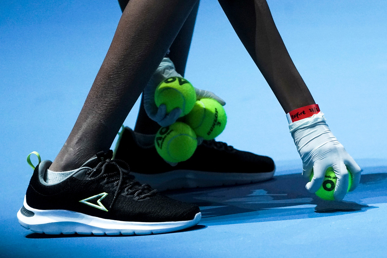 Een ballenjongen aan het werk tijdens de Singapore Tennis Open. Beeld EPA