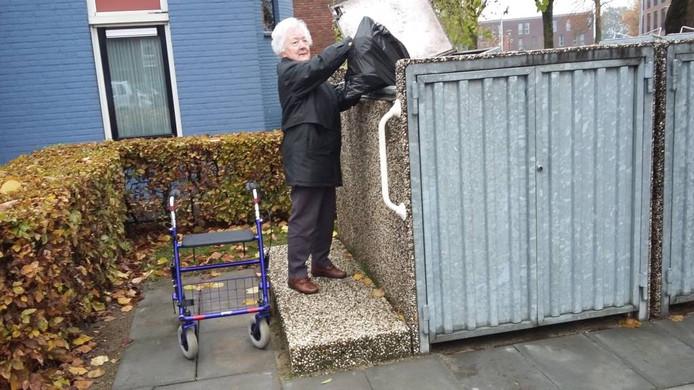 Mevrouw Elisabeth Mondeel (83) bij de afvalcontainer.