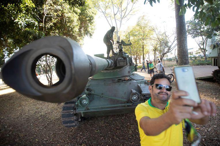 Een aanhanger van Bolsonaro neemt een selfie bij een tank, die deze week als onderdeel van een inderhaast opgetrommelde militaire parade door de hoofdstad reed. Beeld EPA